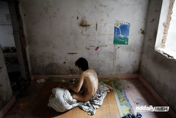 A naked Wu Guilin, a drug addict in Guangdong province of China, sits in his dilapidated home, his legs infected so he can no longer walk upright.