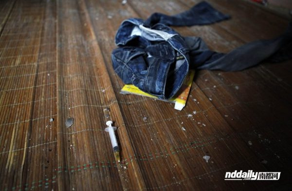 A pair of denim jeans and several drug needles remain in the deceased Wu Guilin's dirty room.