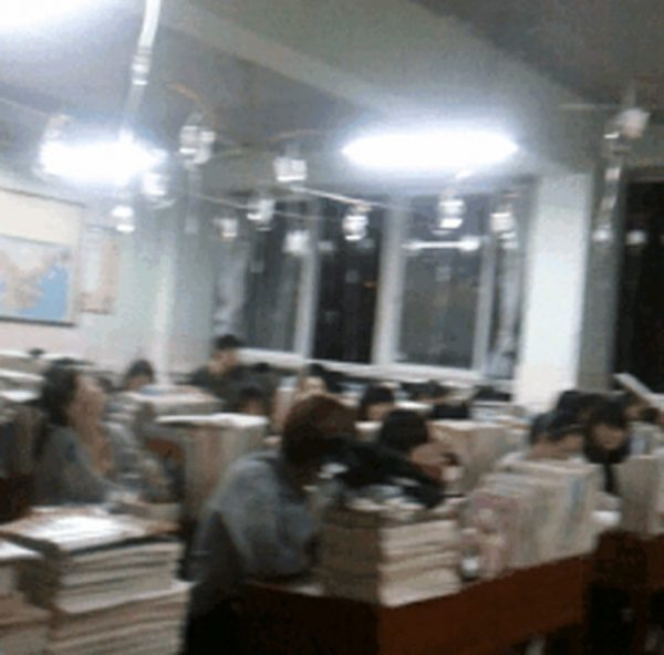 Bottles of IV drips containing amino acids suspended above Chinese students cramming for their Gaokao exams.