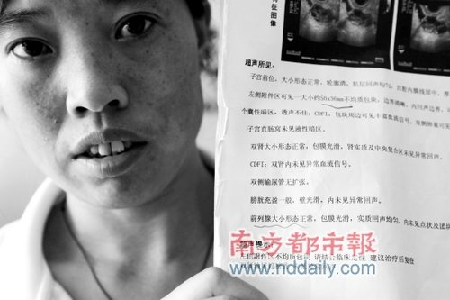 A Chinese woman in Shenzhen holds up her ultrasound report from a local private hospital showing that her prostate is normal.