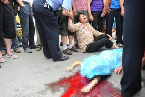 Family wail beside the body of an 11-year-old schoolgirl who had been hit by a speeding black Audi in Xi'an.
