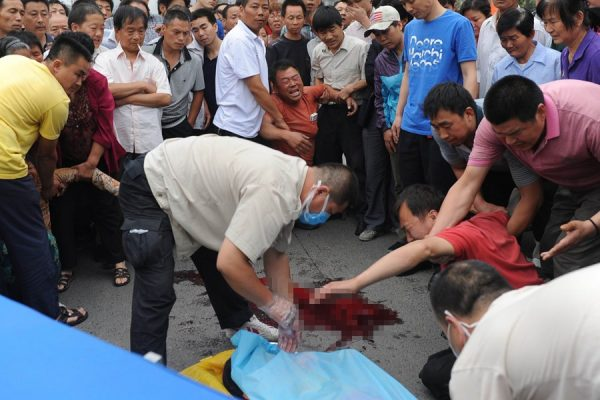 Grieving family at the scene of a traffic accident in Xi'an, China, where a young 11-year-old girl was hit and killed by a speeding black Audi.