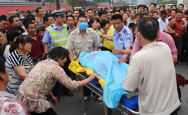 The body of an 11-year-old girl being carried away after being killed by a speeding car in Xi'an, China.