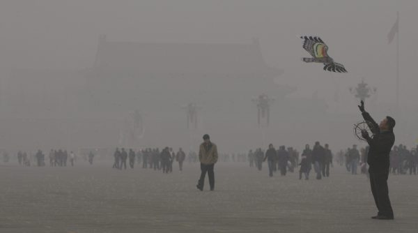 Poor visibility at Tiananmen Square in Beijing due to fog or smog (air pollution), as a Chinese man flies a kite.