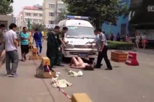 A naked woman, the lady who caused the accident the ambulance is arriving to help with, blocks and obstructs the paramedics from giving aid.