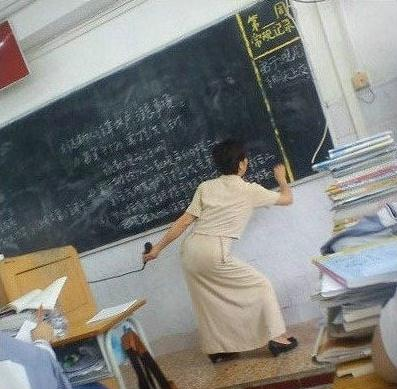 A female Chinese teacher writing on the chalkboard in an awkward position.