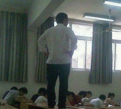 A Chinese teacher standing on a classroom desk.