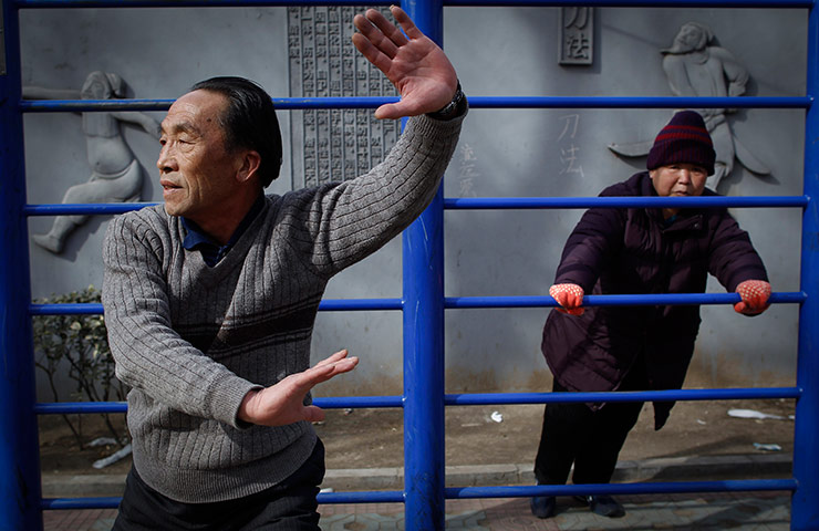 Elderly Chinese practicing taichi and exercising at a park in Beijing.