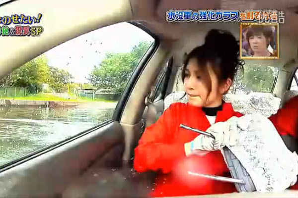 A Japanese television show where a woman learns how to use a headret to break a car's window in a flooding situation.