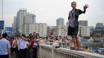 The man is standing on the egde of the bridge.