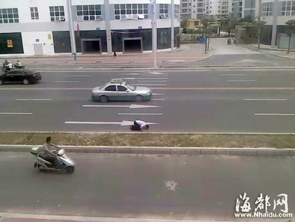 The young man is crawling with his knees and kowtowing in the middle of the road.