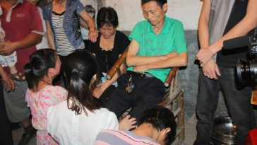 The rescued family kneeling before Deng Jinjie's parents.