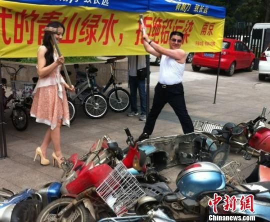 Chen Guangbiao and actress Sun Qian who played Jin Xi in <em>Zeng Huan Zhuan</em> [a popular Chinese costume drama] are smashing scooters powered by lead-acid batteries at the scene as a protest against lead pollution/contaimination. Photographed by Sheng Jie