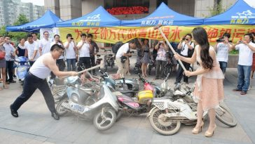Chen Guangbiao and an actress smashing electric scooters and mopeds.