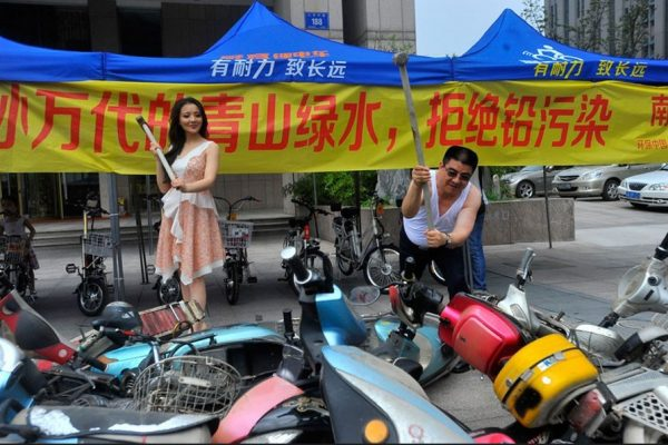 Famed philantropist Chen Guangbiao and an actress smashing lead battery electric scooters in China.