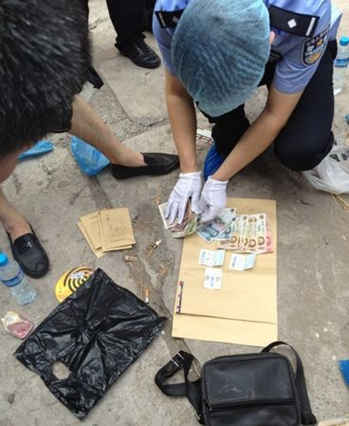 Money and other items found on Chinese serial robber and murderer Zhou Kehua's body after he was shot dead by police in Chongqing.