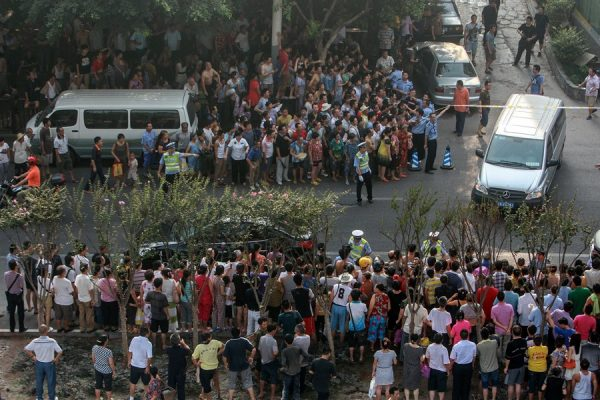 Crowds gathered around the scene where police cornered and shot to death Chinese serial robber and murderer Zhou Kehua in Chongqing.