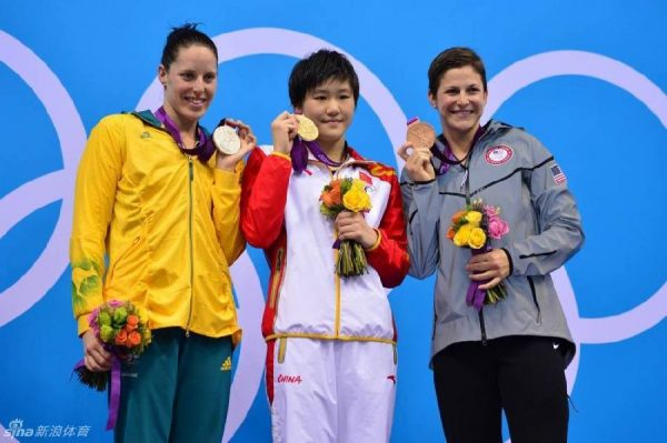 Gold medalist Ye Shiwen of China with silver medalist Alicia Coutts (left) of Australia and bronze medalist Caitlin Leverenz of the U.S. (right) on the podium during the women's 200m individual medley victory ceremony at the London 2012 Olympic Games.