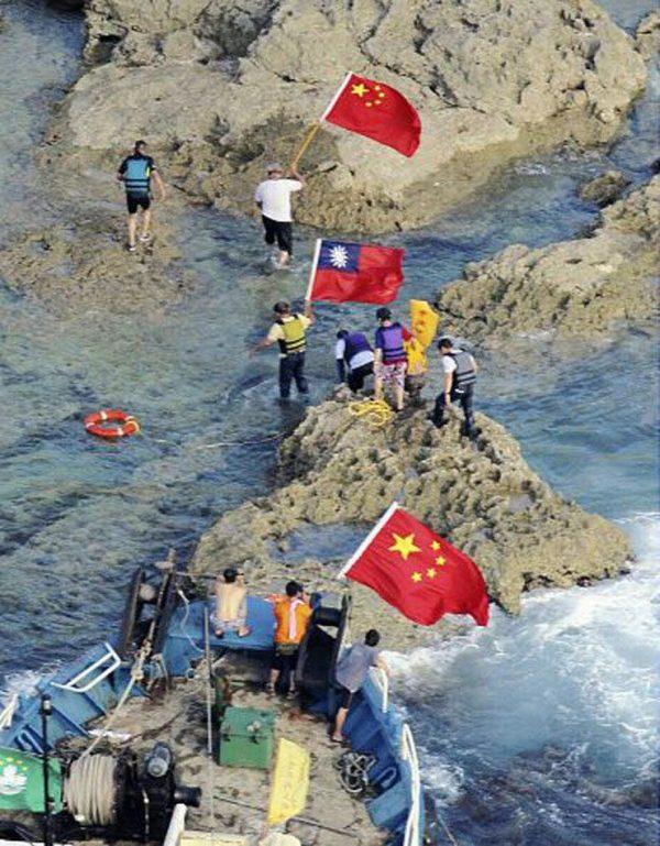 Chinese Diaoyu Island soverignty activists from Hong Kong swimming ashore onto Senkaku Island carrying PRC and ROC national flags.