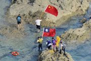 Chinese Diaoyu Island soverignty activists from Hong Kong swimming ashore onto Senkaku Island carrying PRC and ROC national flags.