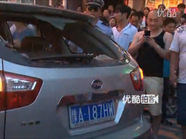 An angry Chinese crowd surrounds a foreigner in a car in Zhengzhou, Henan province, after he allegedly slapped and spat on a local Chinese woman over a minor traffic accident and dispute.