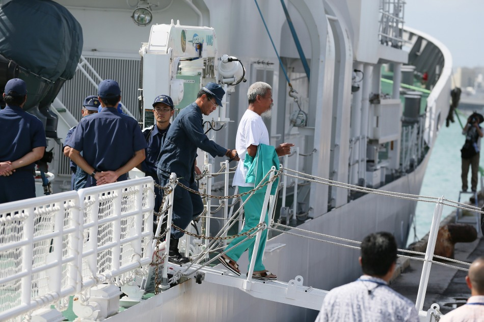 A pro-China activist (C), that landed on the disputed island known as Senkaku in Japan and Diaoyu in China, is arrested by police at Naha port in Japan's sourthern island of Okinawa on August 16, 2012. Japan arrested 14 people after pro-China activists landed on August 15 on an island at the centre of a bitter territorial row in an episode that threatens to further destabilise fractious ties. AFP PHOTO / JIJI PRESS    JAPAN OUT