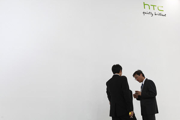 """HTC suits standing beside a white wall with """"HTC: Quietly Brilliant""""."""