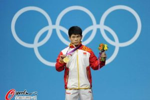 Lin Qingfeng holding up his men's weightlifting gold medal.