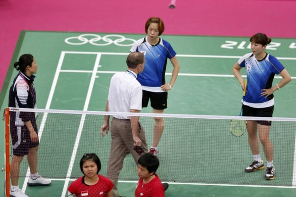 Tournament referee Torsten Berg speaks to players from South Korea and Indonesia during their women's doubles group play stage Group C badminton match during the London 2012 Olympic Games at the Wembley Arena.
