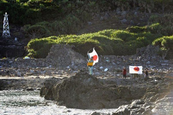 Japanese nationalists waving Japan's national flag on the disputed Senkaku Islands.