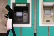 Chinese woman walking away from an Agricultral Bank of China ATM.