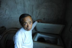 Tian Xueming, a father beside the freezer where he has kept his dead son's body frozen for the past 6 years, ever since his son died from leukemia.