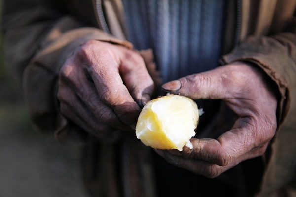A peasant is eating a potato which was provided by his fellow villager.