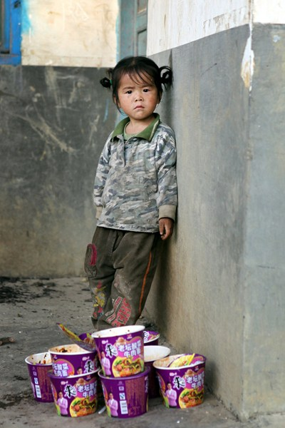 A little girl is standing beside a stack of instant noodles boxes.