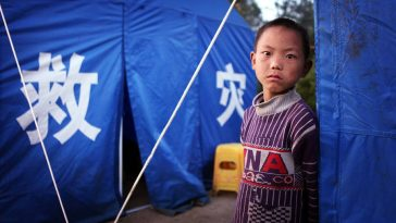 A little child is standing outside relief tents.