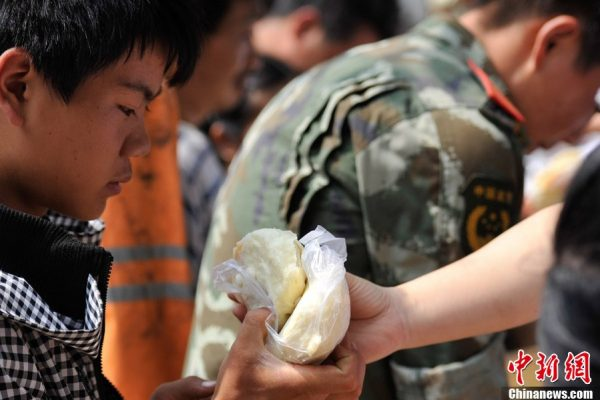 Relief workers are giving out streamed stuffed buns to the people.