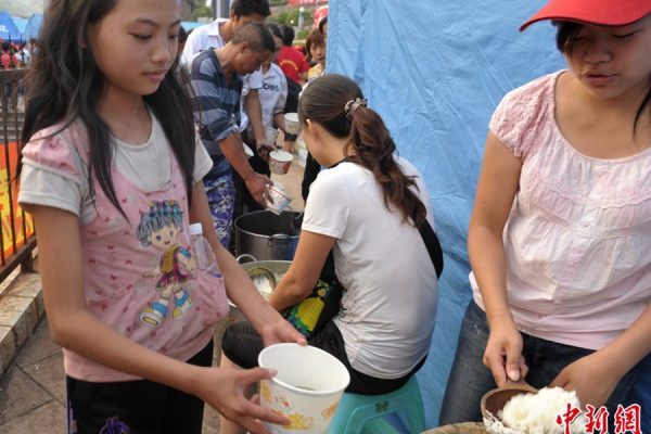 A child is getting free supper in the relocation site.