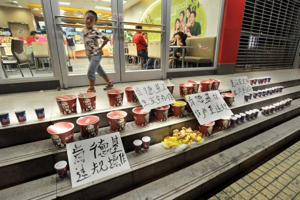 Meal buckets with signs condemning KFC.