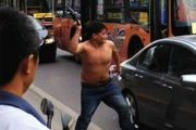 A shirtless Chinese man attacks a Toyota Corolla with a metal u-lock during anti-Japan demonstrations in Xi'an, China.