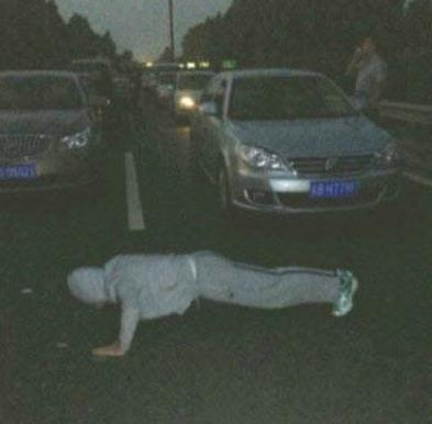 a guy does push-ups during national day traffic jams at night