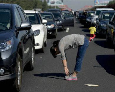 a woman crouches during national day traffic jams