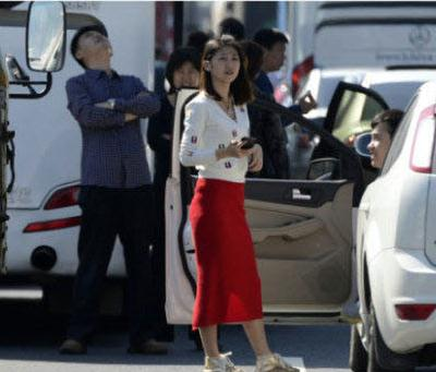 a woman waiting outside the car during national day traffic jams