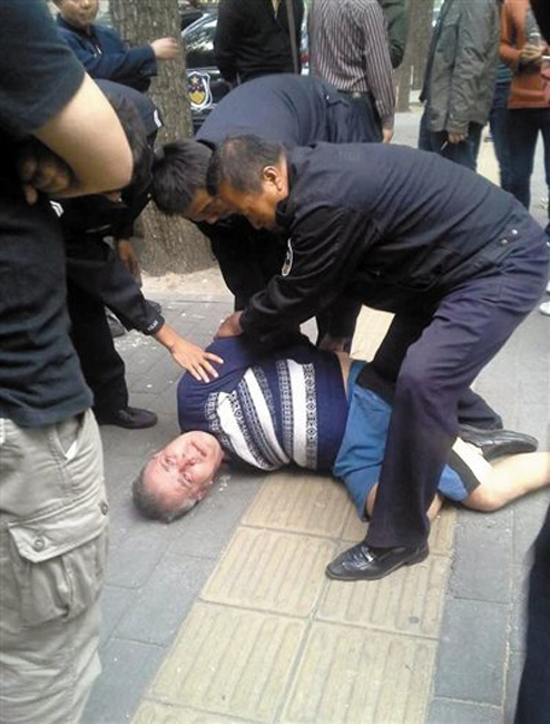 Beijing Police officers subduing and arresting a Russian man who had gone on a druken rampage that involved kitchen knives and stolen cars.