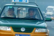 A foreign passenger in a green and yellow Beijing taxi.