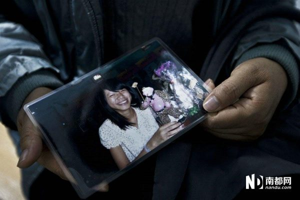 The mother is carrying a picture of Wu Huajing.