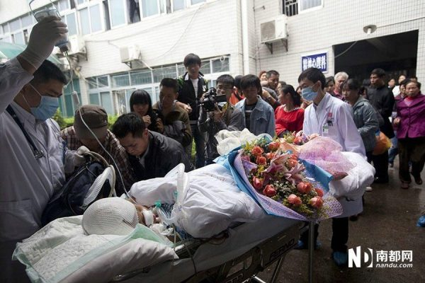 The medical staff is rolling Wu Huajing into the ambulance for hospital transfer.