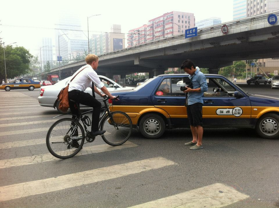 Chris on a bicycle at a Beijing intersection.