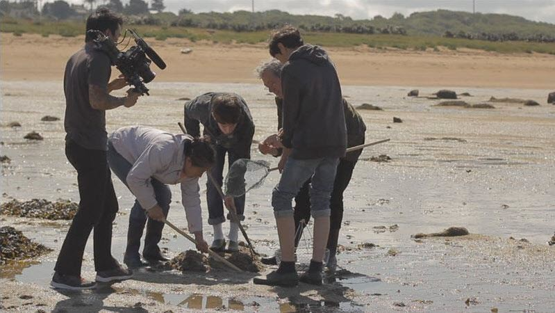 Michel and Qi, along with their children, with filming crew at a beach in France.