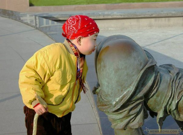 """A boy is """"sniffing"""" a statue's backside."""