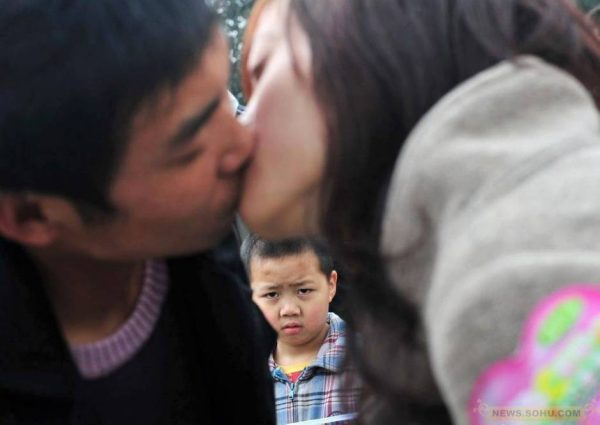 A boy is eyeing a couple kissing each other.